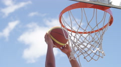 Close up of basketball player's hands slam dunking, in slow motion Stock Footage