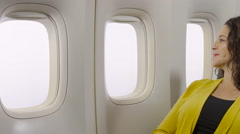 Woman looking out the window of an airplane Stock Footage