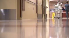 Orderly moves a machine down hospital hall Stock Footage