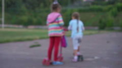 Children playing kick scooter Stock Footage