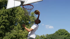 Basketball player doing a fancy 360 degree slam dunk, in slow motion Stock Footage