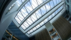 Timelapse of sky and clouds through the glass roof of modern office building Stock Footage