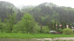 4K Summer rain storm on mountain green forest tree heavy fog traditional house Stock Footage