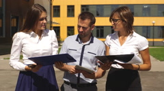 Three colleagues discussing work in an innovative town Stock Footage