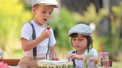 Two adorable children, boy brothers, blowing candles on a cake on birthday pa Stock Footage