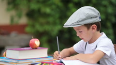Boy, writing his homework from school, drawing and writing in his notebook, l Stock Footage
