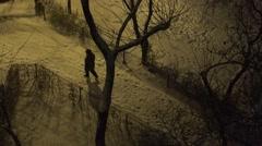 4K Aerial view pedestrian people walk on snowy sidewalk in park cold night snow Stock Footage