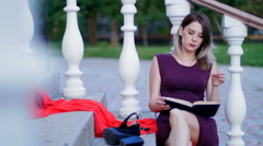 Beautiful girl reading a book sitting on the stairs Stock Footage