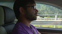 Portrait of man driving car and smoking sigarette Stock Footage