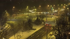 4K Aerial view snow fall on urban town blizzard and car traffic roundabout road Stock Footage