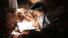 Sweet child, boy, reading a book on the attic on a house, sitting on a hay of Stock Footage