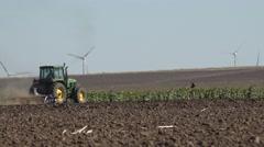 4k Industrial tractor plough field in autumn season near wind turbine working Stock Footage