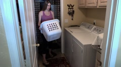 Young Pregnant Woman Loads Clothes into Dryer Stock Footage