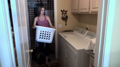 Young Pregnant Woman Puts Clothes into Washer Stock Footage