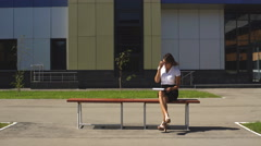 Businesswoman sitting on a bench at lunchtime and talking on the phone Stock Footage