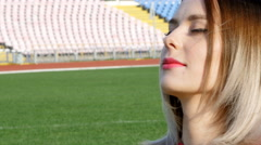 Girl sitting in the middle of a football field - winking eye Arkistovideo