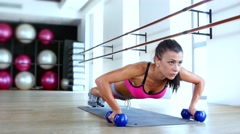 Brunette woman at gym push up push-up workout exercise with dumbbells Stock Footage