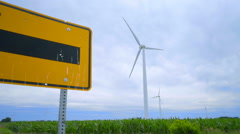 Wind turbine generator on green farm field. Road sign pointing on wind turbines Stock Footage