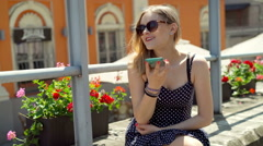 Happy girl sitting in the town and chatting on loudspeaker Stock Footage