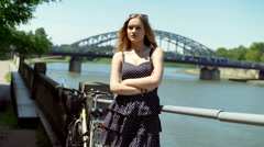 Pretty girl standing next to the river and looking to the camera Stock Footage