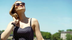 Pretty girl wearing vintage sunglasses and enjoying sun in the town, steadycam s Stock Footage