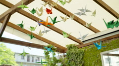 View of the colorful, origiami birds hanging on the cafe's roof Stock Footage