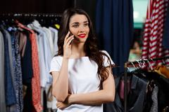 Young beautiful girl speaking on phone in shopping mall Stock Photos