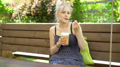 Pretty girl swinging on the wooden swing and drinking frappe Stock Footage