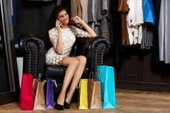 Girl speaking on phone, sitting in shopping mall with buyings Stock Photos