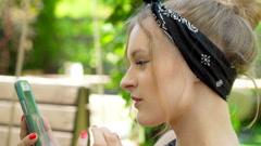 Happy girl in bandanna browsing internet on smartphone, steadycam shot Stock Footage