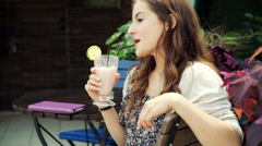 Pretty, romantic girl looking thoughtful while drinking cocktail, steadycam shot Stock Footage