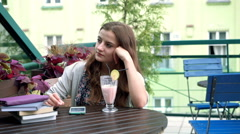 Romantic girl sitting at the wooden table and looking very thoughtful Stock Footage