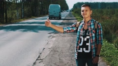 Young man with backpack hitchhiking at road in countryside. Thumbing up. Sunny Stock Footage