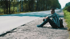 Man sit at road in countryside. Hitchhiking. Waiting for help. Smoking cigarette Stock Footage