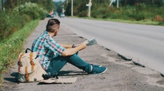 Man sit at road in countryside. Hitchhiking. Waiting. Looking map. Sunny day Stock Footage