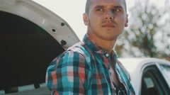Sad man at broken car with opened capote at road in countryside. Problem Stock Footage
