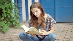 Pretty girl reading book and looking to the camera while sitting on the ground Stock Footage