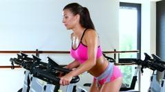 Sporty woman riding stationary bike in gym Stock Footage