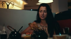 Brunette young girl sit at table in sushi restaurant. Smile. Talk with someone Stock Footage