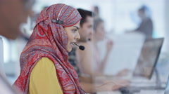 4K Mixed ethnicity telesales team working together in busy call center Stock Footage