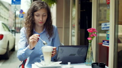 Girl sitting in the outdoor cafe and adding sugar to latte Stock Footage