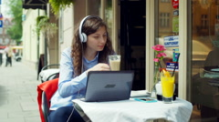 Girl listening music and drinking latte while using laptop in the cafe Stock Footage