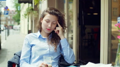 Girl having a hadache and looking morose in the outdoor cafe Stock Footage