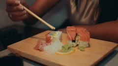 Brunette girl sitting at table in restaurant. Smile. Eat sushi by chopsticks Stock Footage