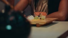 Brunette girl sitting at table in japanese restaurant. Eat sushi by chopsticks Stock Footage