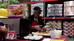 Saleswoman offering spring roll food samples to customers inside Costco store. Stock Footage