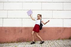 Young beautiful female student in glasses walking down street, holding folders Stock Photos