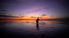 Silhouette of a Balinese fisherman casting a traditional fishing net at sunset Stock Footage