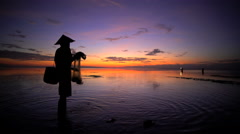 Balinese fisherman throwing traditional net into the Indian ocean at sunset Stock Footage