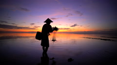 Balinese fisherman in silhouette throwing net into the ocean on a sunset beach Stock Footage